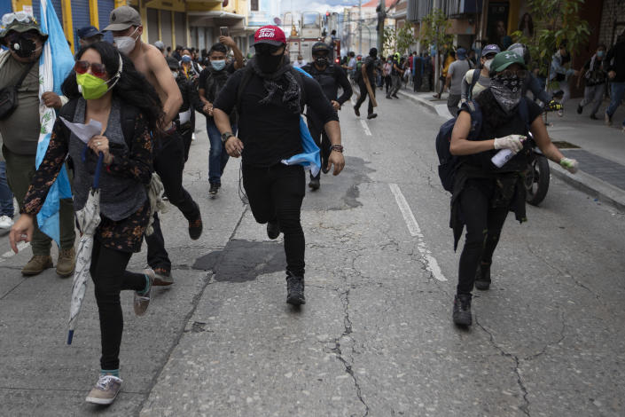 Protestors take chase from advancing police after protesters set a part of the Congress building on fire, in Guatemala City, Saturday, Nov. 21, 2020. Hundreds of protesters were protesting in various parts of the country Saturday against Guatemalan President Alejandro Giammattei and members of Congress for the approval of the 2021 budget that reduced funds for education, health and the fight for human rights. (AP Photo/Oliver De Ros)