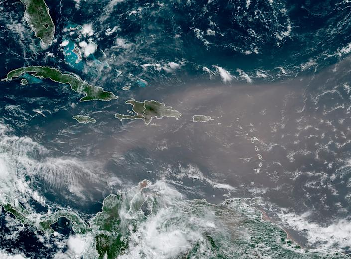 A satellite photo shows a cloud of dust from the Sahara Desert arriving in the Caribbean on Monday. The massive cloud of dust is blanketing the Caribbean as it heads to the U.S. with a size and concentration level that meteorologists say hasn't been seen in about half a century.