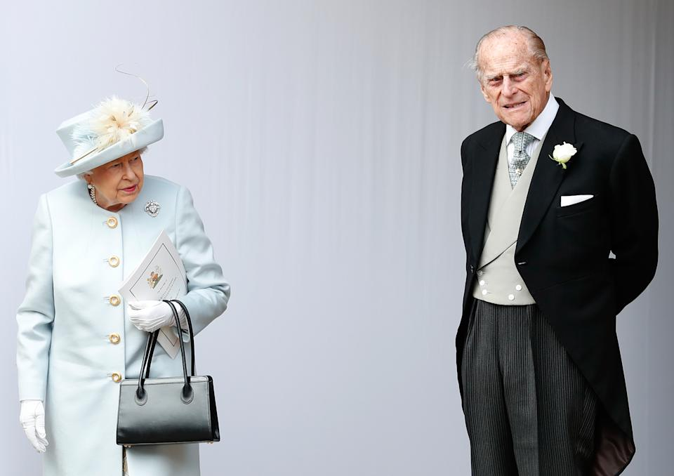 TOPSHOT - Britain's Queen Elizabeth II (L) and Britain's Prince Philip, Duke of Edinburgh (R) wait for the carriage carrying Princess Eugenie of York and her husband Jack Brooksbank to pass at the start of the procession after their wedding ceremony at St George's Chapel, Windsor Castle, in Windsor, on October 12, 2018. (Photo by Alastair Grant / POOL / AFP)        (Photo credit should read ALASTAIR GRANT/AFP via Getty Images)