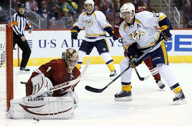 Phoenix Coyotes' Thomas Greiss (1), of Germany, makes a save on a shot by Nashville Predators' Patric Hornqvist (27), of Sweden, as Predators' David Legwand watches during the first period of an NHL hockey game Thursday, Oct. 31, 2013, in Glendale, Ariz. (AP Photo/Ross D. Franklin)