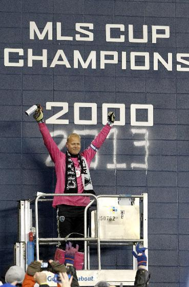 Sporting Kansas City goalkeeper Jimmy Nielsen acknowledges the fans after spray painting on the MLS Cup wall at Sporting Park after defeating Real Salt Lake in a shoot out in the MLS Cup final soccer match in Kansas City, Kan., Saturday, Dec. 7, 2013. (AP Photo/Colin E. Braley)