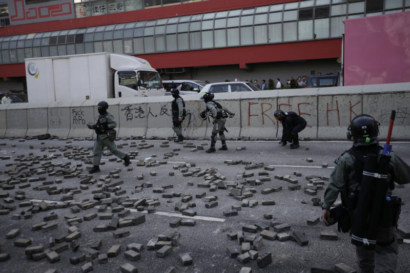 Police walk past a road scattered with bricks to block traffic in Hong Kong on Monday, Nov. 11, 2019. A Hong Kong protester was shot by police Monday in a dramatic scene caught on video as demonstrators blocked train lines and roads during the morning commute. (AP Photo/Dita Alangkara)