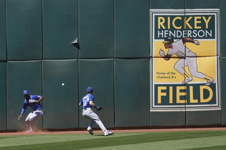 An RBI-double hit by Oakland Athletics' Mark Canha falls between Kansas City Royals center fielder Michael A. Taylor, left, and left fielder Andrew Benintendi during the sixth inning of a baseball game in Oakland, Calif., Sunday, June 13, 2021. (AP Photo/Jeff Chiu)