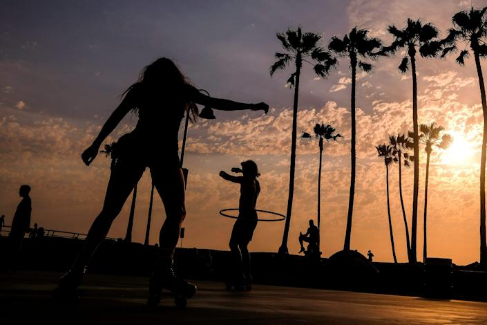 People are pictured as they workout near Venice Beach on Wednesday. An unusually early and long-lasting heat wave brought more triple-digit temperatures to a large swath of the Western United States, raising concerns that such extreme weather could become the new normal amid a decades-long drought.