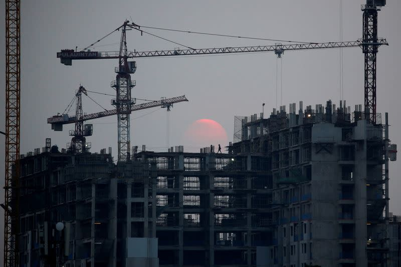 A worker walks at a construction site during dusk in Jakarta