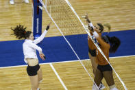 Texas' Brionne Butler (10) and Molly Phillips (15) block a spike from Wisconsin's Dana Rettke, left, during a semifinal in the NCAA women's volleyball championships Thursday, April 22, 2021, in Omaha, Neb. (AP Photo/John Peterson)