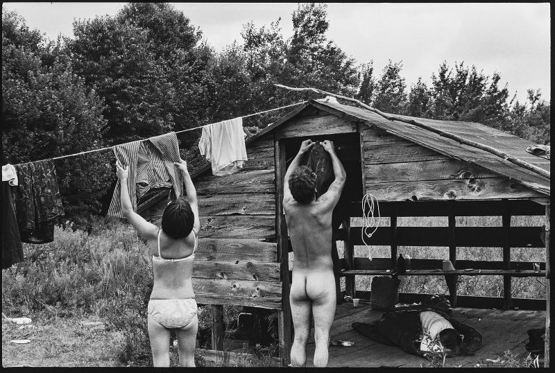 A couple hanging clothes out to dry on a hillside away from the crowd at Woodstock, in 1969. | Burk Uzzle