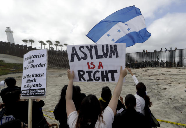 <p>Central American migrants sit on top of the border wall on the beach in San Diego during a gathering of migrants living on both sides of the border, April 29, 2018. (Photo: Chris Carlson/AP) </p>