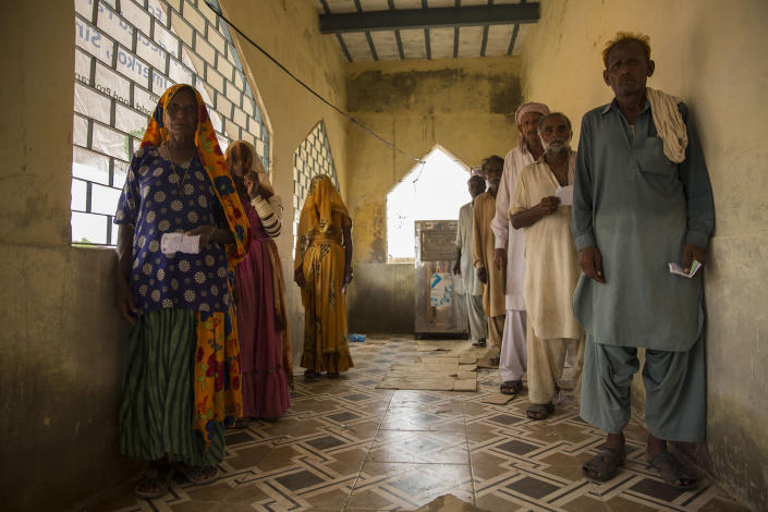 Families wait to receive WFP ration packages in UmerkotSaiyna Bashir/Arete/WFP
