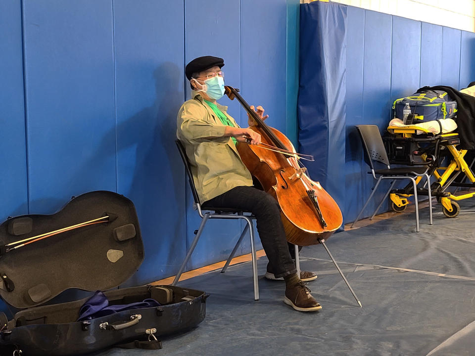 This photo provided by Berkshire Community College shows cellist Yo-Yo Ma performing at Berkshire Community College's second dose Pfizer vaccination clinic in the Paterson Field House on Saturday, March 13, 2021 in Pittsfield, Mass. Newly vaccinated Massachusetts residents were treated to a mini concert when the famed cellist brought out his instrument after getting his second shot. (Jonah Sykes/Berkshire Community College via AP)