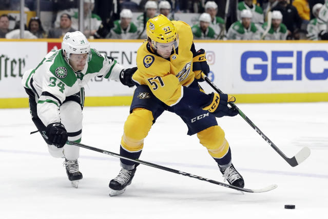 Dallas Stars right wing Denis Gurianov (34), of Russia, pokes the puck away from Nashville Predators defenseman Dante Fabbro (57) in the second period of an NHL hockey game, Saturday, Dec. 14, 2019, in Nashville, Tenn. (AP Photo/Mark Humphrey)