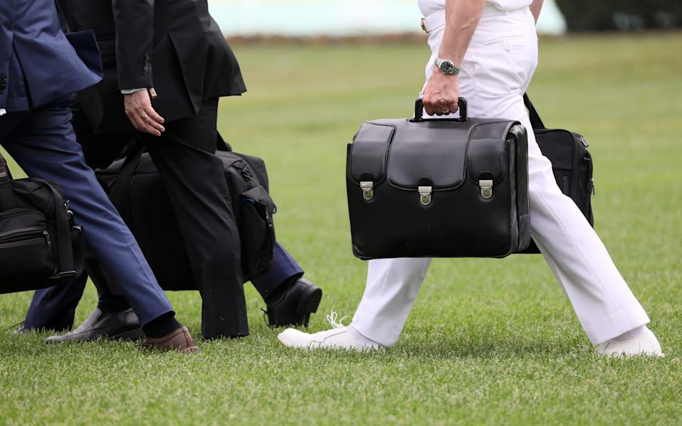 """A military aide carries the nuclear """"football"""" as he walks to board Marine One with President Trump - Reuters"""