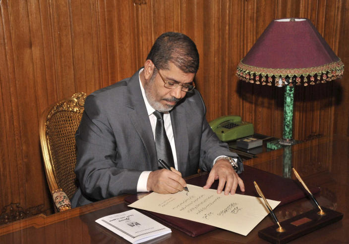 In this image released by the Egyptian Presidency and taken late Tuesday, Dec. 25, 2012, President Mohammed Morsi signs into law the country's Islamist-backed constitution. Egypt's government asked parliament Wednesday to prioritize legislation to organize parliamentary elections, regulate the media and fight corruption as the upper chamber held its first session with temporary new powers granted by the constitution.(AP Photo/Egyptian Presidency)