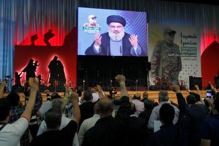 Hezbollah leader Sayyed Hassan Nasrallah addresses his supporters from a screen, during a ceremony marking a year after Hezbollah commander Mustafa Badreddine(picture on banner) was killed in an attack in Syria, in Beirut's southern suburbs, Lebanon May 11, 2017. REUTERS/Aziz Taher