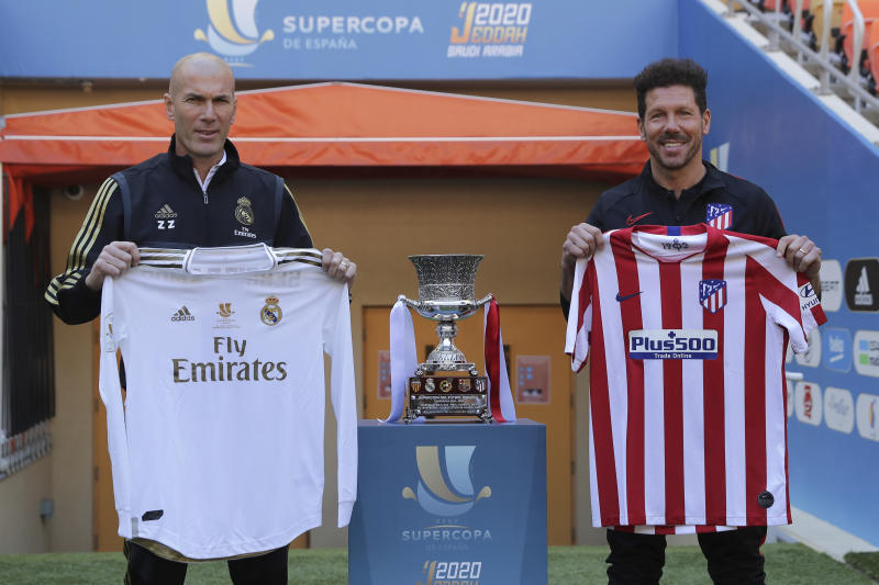 Atletico Madrid's head coach Diego Simone, right, stands with Real Madrid's head coach Zinedine Zidane during the trophy photo call at King Abdullah stadium, in Jiddah, Saudi Arabia, Saturday, Jan. 11, 2020, ahead of their Spanish Super Cup Final soccer match between Real Madrid and Atletico Madrid on Sunday. (AP Photo/Hassan Ammar)
