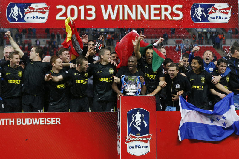 Wigan Athletic's players celebrate with their trophy after their win against Manchester City at the end of their English FA Cup final soccer match at Wembley Stadium, London, Saturday, May 11, 2013. (AP Photo/Matt Dunham)