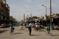 A man walks as others ride bicycles on a street in Falluja