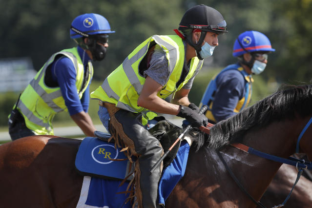 Riders wearing masks workout horses at Belmont Park in Elmont, N.Y., Wednesday, June 17, 2020. The 152nd running of the Belmont Stakes is scheduled to be run on Saturday. (AP Photo/Seth Wenig)