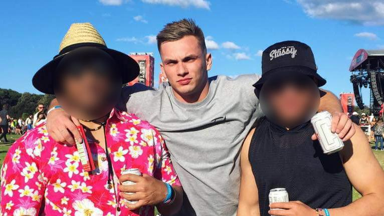 Glenn Mcrae, 24, pictured at a music festival in 2016 with two friends. Both of their faces are blurred.