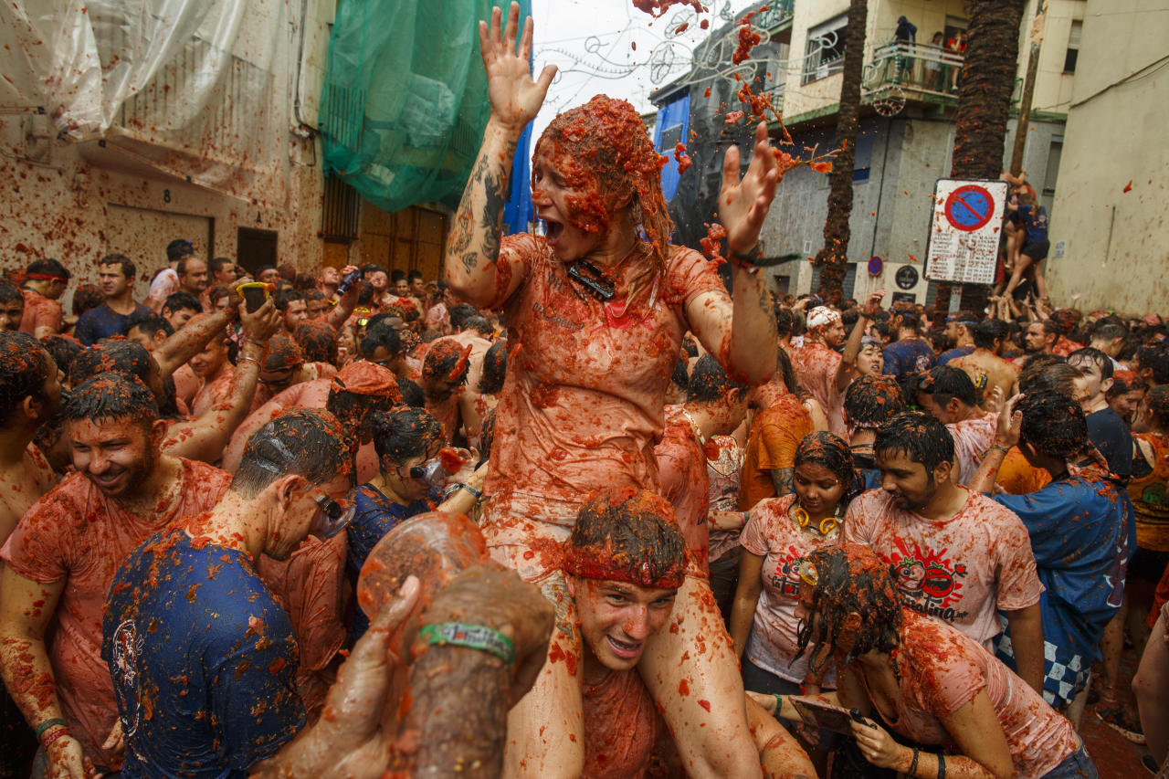 <p>Revellers enjoy the atmosphere in tomato pulp while participating the annual Tomatina festival on Aug. 30, 2017 in Bunol, Spain. An estimated 22,000 people threw 150 tons of ripe tomatoes in the world's biggest tomato fight held annually in this Spanish Mediterranean town. (Photo: Pablo Blazquez Dominguez/Getty Images) </p>