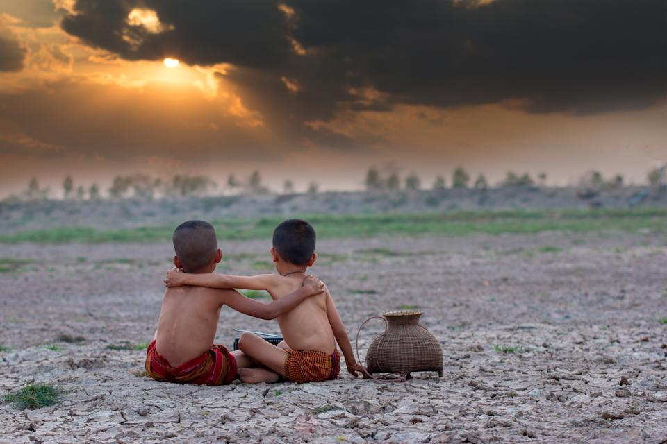Sad a boy with friend sitting on dry ground.Concept hope and drought.Asia.