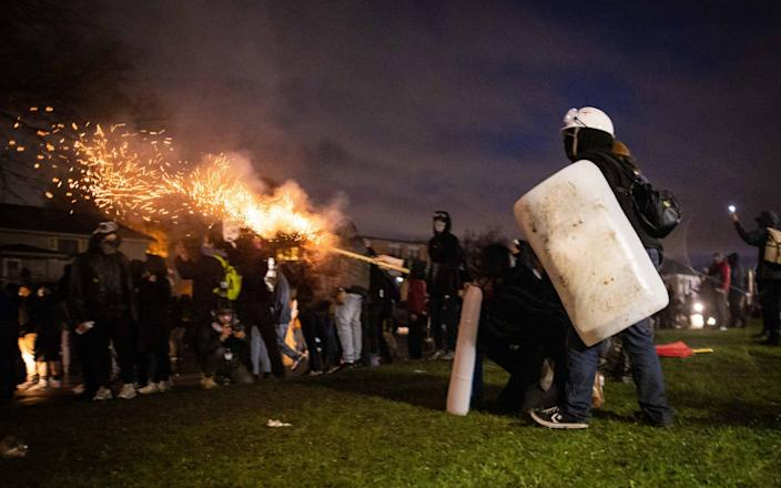 Demonstrators launch fireworks towards members of the National Guard during a protest in Brooklyn Center