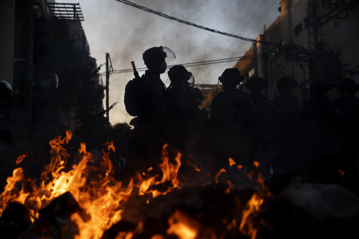 Israeli police officers stand guard next to burning garbage during clashes with ultra-Orthodox Jews in Bnei Brak, Israel, Sunday, Jan. 24, 2021. Ultra-Orthodox demonstrators clashed with Israeli police officers dispatched to close schools in Jerusalem and Ashdod that had opened in violation of coronavirus lockdown rules, on Sunday. (AP Photo/Oded Balilty)