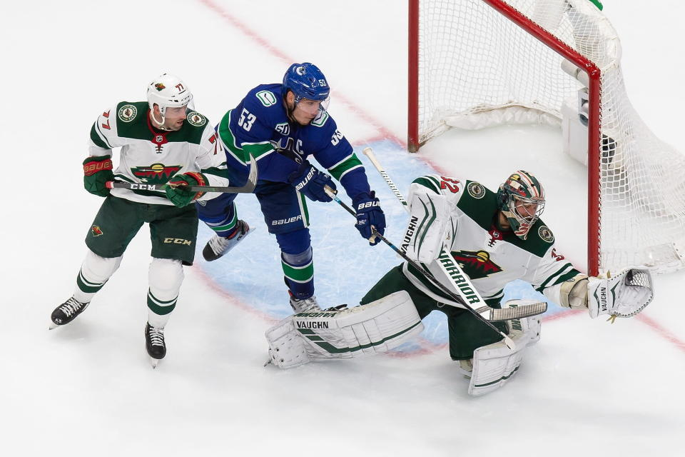 Minnesota Wild goaltender Alex Stalock (32) makes a save against Vancouver Canucks' Bo Horvat (53) as Wild's Brad Hunt (77) defends during the second period of an NHL hockey playoff game in Edmonton, Alberta, Tuesday, Aug. 4, 2020. (Codie McLachlan/The Canadian Press via AP)