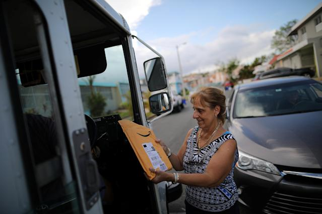 <p>A local resident receives a package from the U.S. Postal Service at an area affected by Hurricane Maria in San Juan, Puerto Rico, Oct. 6, 2017. (Photo: Carlos Barria/Reuters) </p>