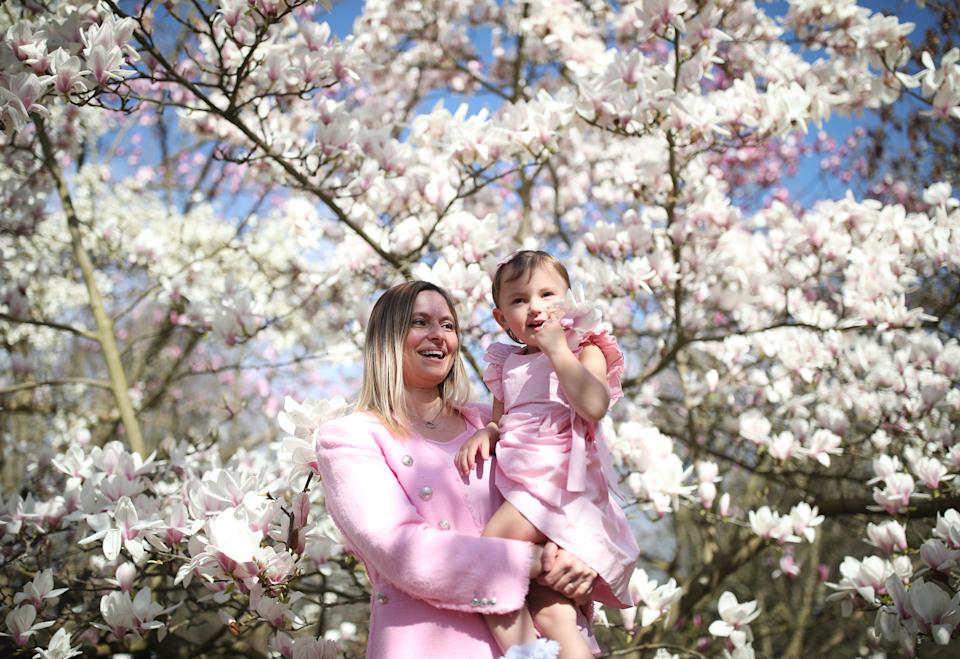 Tanya Szavejcsuk and her daughter Mia, aged 2, pose next to a magnolia tree at at Kew Gardens in south-west London. Picture date: Tuesday March 30, 2021. Temperatures in parts of the UK are expected to be significantly warmer this week as families and friends are reunited and sporting activities are allowed to resume in England.