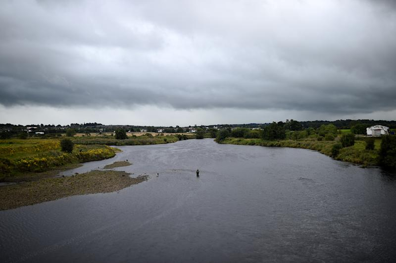 A man fishes in the river Foyle which marks the border between Ireland on the right and Northern Ireland on the left, in Strabane, Northern Ireland, August 16, 2017. REUTERS/Clodagh Kilcoyne