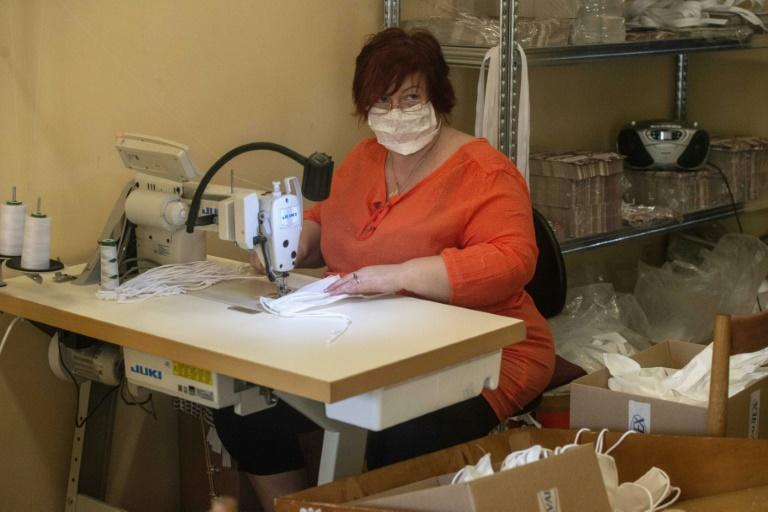 A woman sews masks in the workshop of a small Czech company as tens of thousands of Europeans join forces via social media to combat a dire global shortage