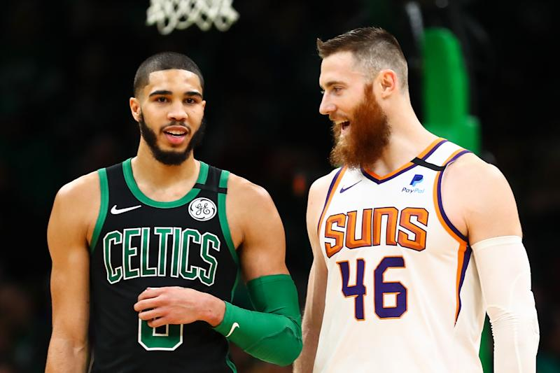 Former teammates Aron Baynes of the Phoenix Suns and Jayson Tatum of the Boston Celtics talk during a game.