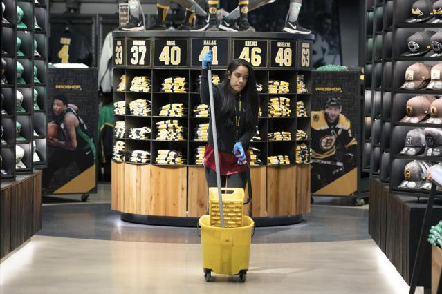 A cleaning person works in the pro shop selling merchandise for both the Boston Celtics and the Bruins at TD Garden in Boston, Saturday, March, 14, 2020. The NBA and the NHL, along with most major sports and sporting events in the United States have suspended play due to concern about the new coronavirus. For most people, the new coronavirus causes only mild or moderate symptoms, such as fever and cough. For some, especially older adults and people with existing health problems, it can cause more severe illness, including pneumonia. The vast majority of people recover from the new virus. (AP Photo/Michael Dwyer)