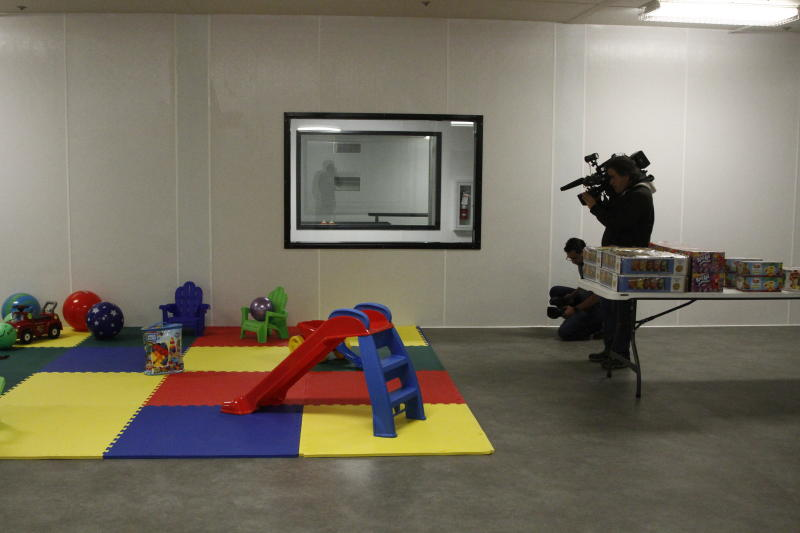 Video journalists record images of never-touched toys during a Border Patrol tour of an immigration holding facility, Tuesday, Feb. 25, 2020, in El Paso, Texas. The complex of modular buildings is expected to open next week. Itcan house and process 1,040 and will replace tents hastily erected for processing last spring. (AP Photo/Cedar Attanasio)