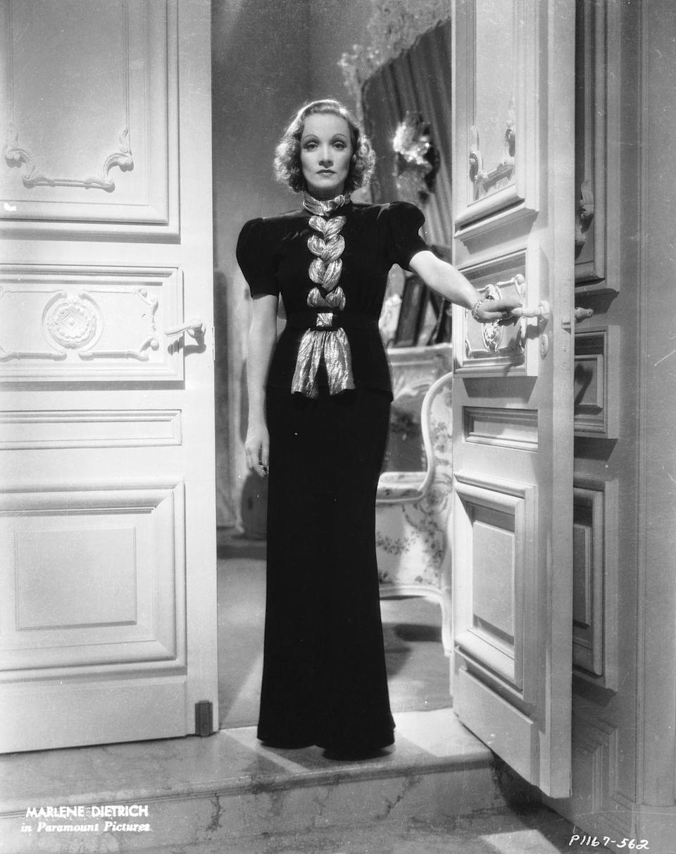 <p>Here, in a scene from <em>Angel</em>, Dietrich, who officially became an American citizen in 1939, wears a black evening gown with a metallic braided accent. <br></p>