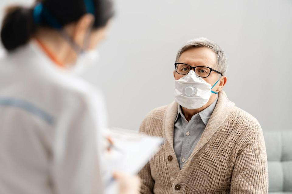 Doctor and senior man wearing facemasks during coronavirus and flu outbreak