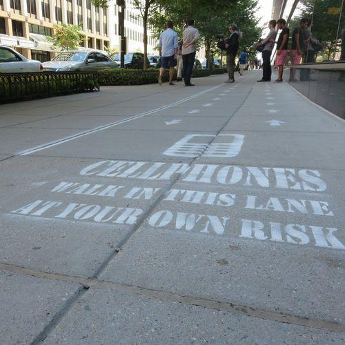 Street stenciled with 'CELLPHONES WALK IN THIS LANE AT YOUR OWN RISK