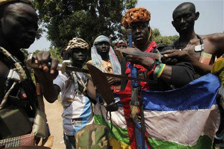 """Fighters from the Christian """"anti-balaka"""" militia gesture with their weapons at their headquarters in the northern Bangui suburb of Boeing, an area near the Mpoko International Airport of Bangui February 22, 2014. REUTERS/Luc Gnago"""