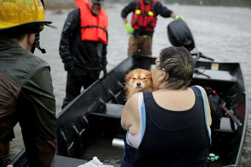Rescue workers from Township No. 7 Fire Department and volunteers from the Civilian Crisis Response Team use a boat to rescue a woman and her dog from their flooded home.