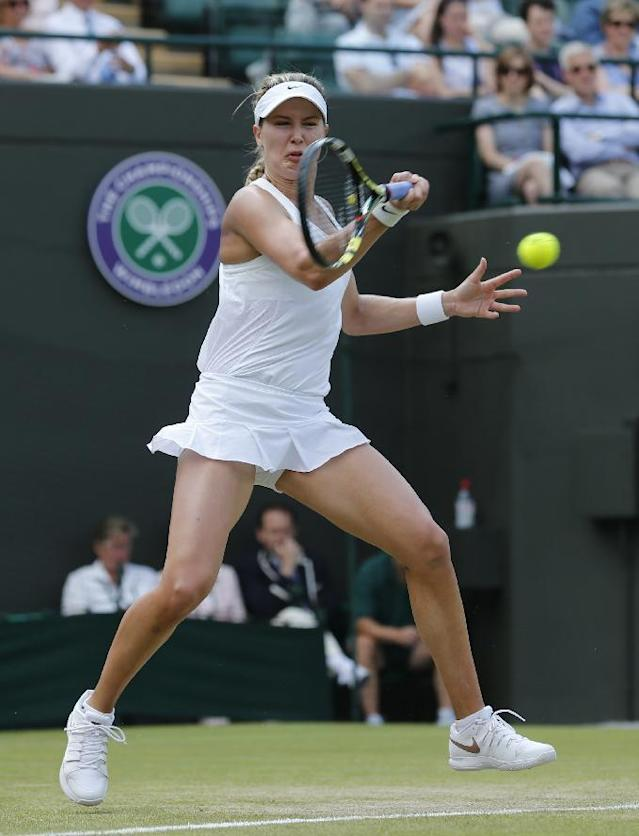 Eugenie Bouchard of Canada plays a return to Angelique Kerber of Germany during their women's singles quarterfinal match at the All England Lawn Tennis Championships in Wimbledon, London, Wednesday, July 2, 2014. (AP Photo/Ben Curtis)