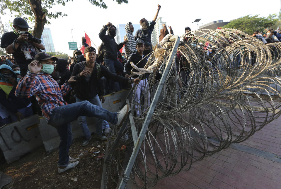 Student protesters try to bring down razor wire barricade set up by the police during a clash in Jakarta, Indonesia, Monday, Sept. 30, 2019. Thousands of Indonesian students resumed protests on Monday against a new law they say has crippled the country's anti-corruption agency, with some clashing with police. (AP Photo/Tatan Syuflana)