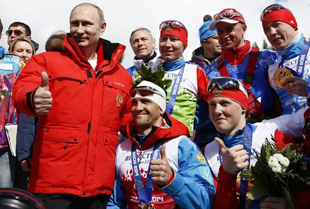 Russian President Vladimir Putin poses with Russian athletes, winners of cross country 4x2.5km open relay at the 2014 Winter Paralympic, Saturday, March 15, 2014, in Krasnaya Polyana, Russia. (AP Photo/Dmitry Lovetsky)