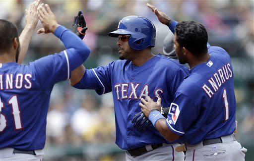 Texas Rangers' Nelson Cruz, center, celebrates with Elvis Andrus (1) and Robinson Chirinos, left, after hitting a three-run home run off Oakland Athletics' Jesse Chavez in the fifth inning of a baseball game on Wednesday, May 15, 2013, in Oakland, Calif. (AP Photo/Ben Margot)