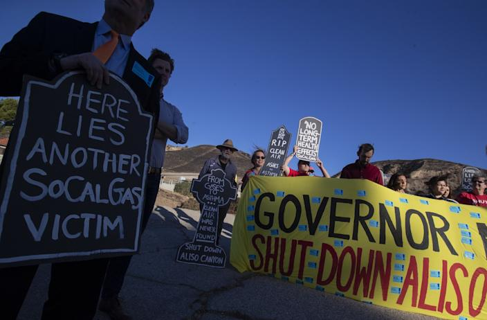 "San Fernando Valley residents hold signs at an Oct. 23 rally marking the fourth anniversary of the blowout at Aliso Canyon, a gas storage facility owned by SoCalGas, in the Porter Ranch neighborhood of Los Angeles. <span class=""copyright"">(Brian van der Brug / Los Angeles Times)</span>"