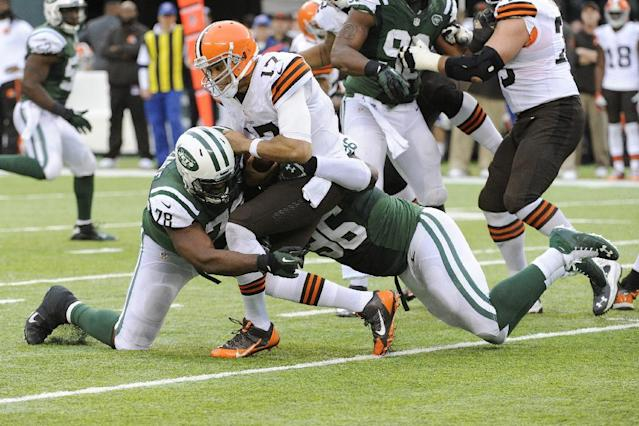 Cleveland Browns quarterback Jason Campbell (17) is sacked by New York Jets' Muhammad Wilkerson (96) and Leger Douzable (78) during the second half of an NFL football game on Sunday, Dec. 22, 2013, in East Rutherford, N.J. The Jets won the game 24-13. (AP Photo/Bill Kostroun)