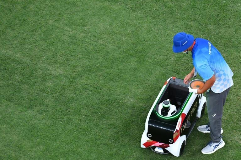 A volunteer puts a discus into a remote-controlled car at the Tokyo Olympics