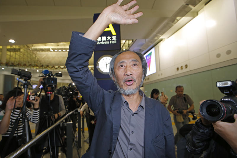"""Chinese dissident writer Ma Jian waves to media after arriving Hong Kong international airport, Friday, Nov. 9, 2018. Despite Mallet's rejection, Hong Kong on Friday permitted dissident writer Ma to enter to attend a literary festival, even after an arts venue in the city canceled his appearance. Ma, whose novels frequently satirize China's communist leaders, told reporters he experienced nothing unusual while passing through passport control and that organizers were still lining-up a place for him to speak. """"The lecture will definitely happen. If there is a single Hong Kong person who is willing to listen, or a single reader who contacts me, I will be there,"""" Ma said. (AP Photo/Kin Cheung)"""