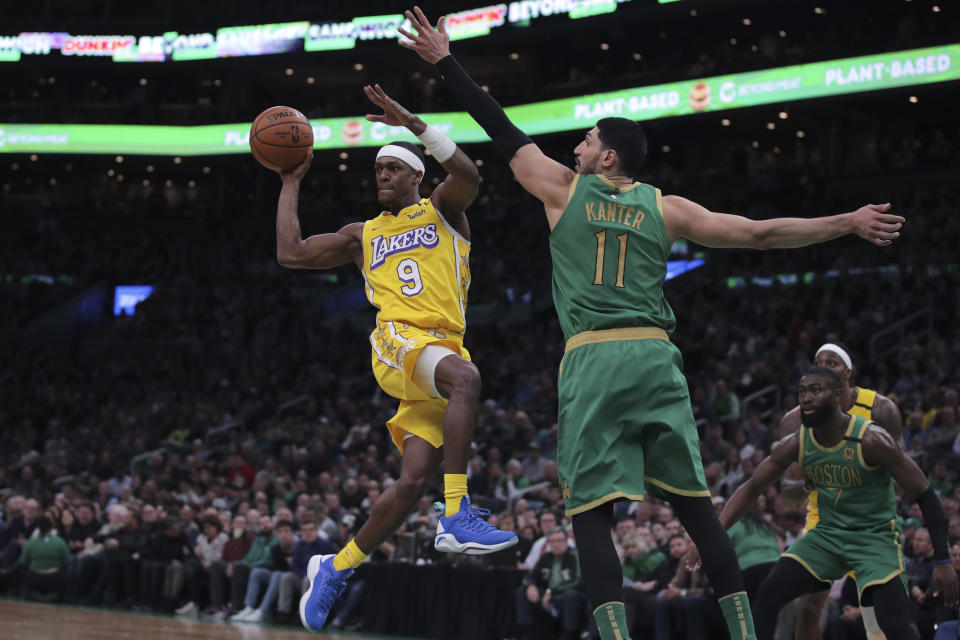 Los Angeles Lakers guard Rajon Rondo (9) passes the ball as he is pressured by Boston Celtics center Enes Kanter (11) during the fourth quarter of an NBA basketball game in Boston, Monday, Jan. 20, 2020. (AP Photo/Charles Krupa)