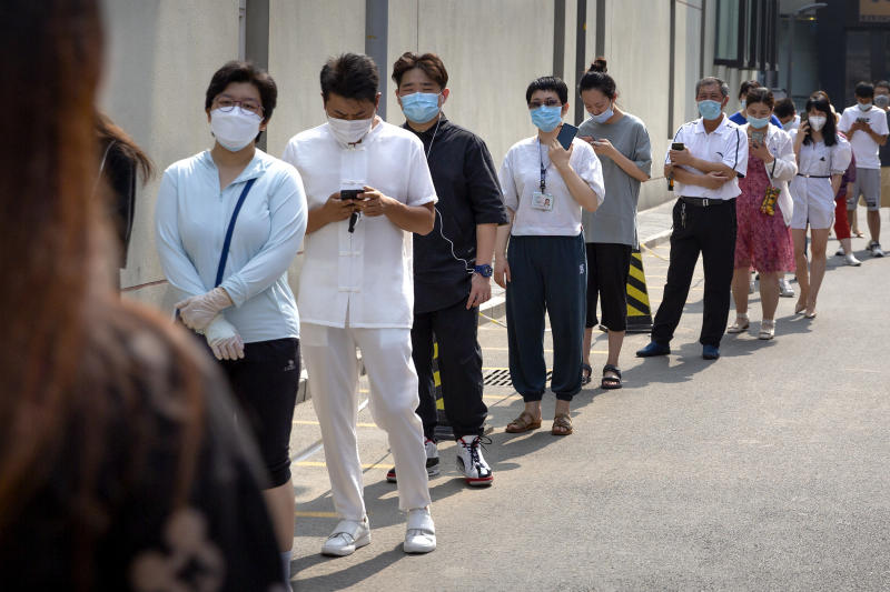 People wearing face masks stand in line for coronavirus tests at a community health clinic in Beijing, Sunday, June 28, 2020. China reported more than a dozen of new confirmed cases of COVID-19 on Sunday, all but a few of them from domestic transmission in Beijing, which has seen a recent spike in coronavirus infections. But authorities in the Chinese capital say a campaign to conduct tests on employees at hair and beauty salons across the city has found no positive cases so far, in a further sign that the recent outbreak has been largely brought under control. (AP Photo/Mark Schiefelbein)